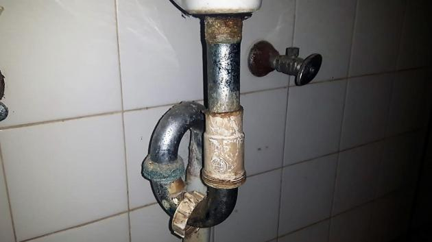 Damaged and rusty trap below bathroom sink | Credit: Philmore Thompson